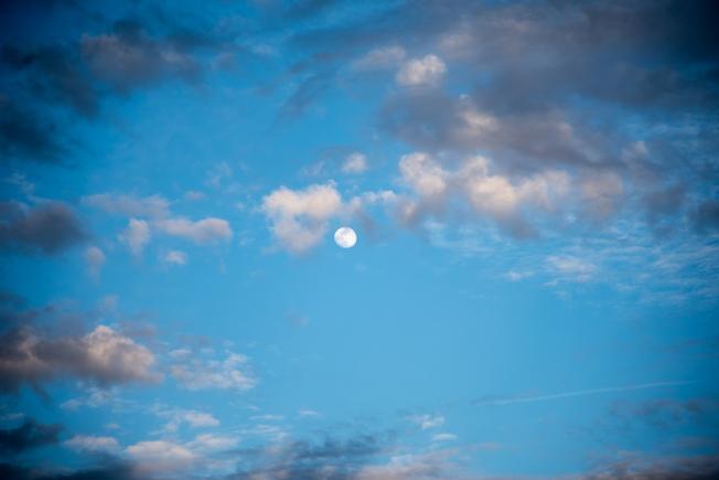 Ciel bleu avec des nuages blancs et gris et la lune au milieu