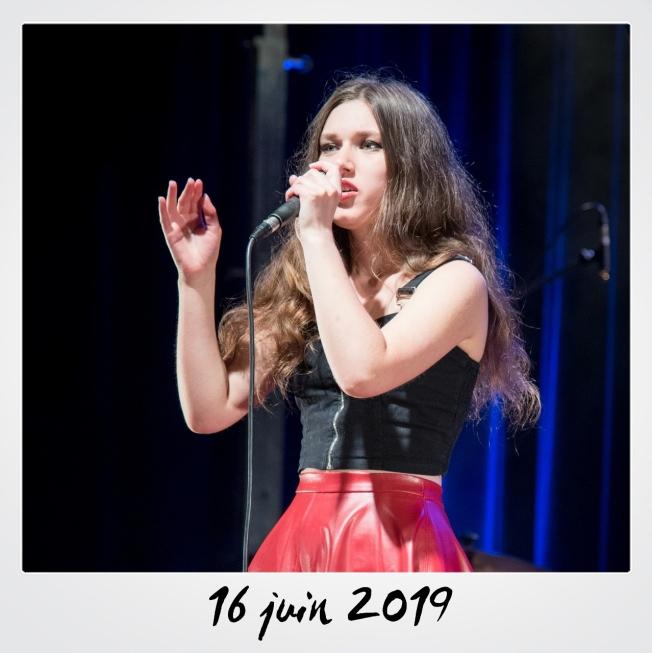 Une jeune femme chante au micro
