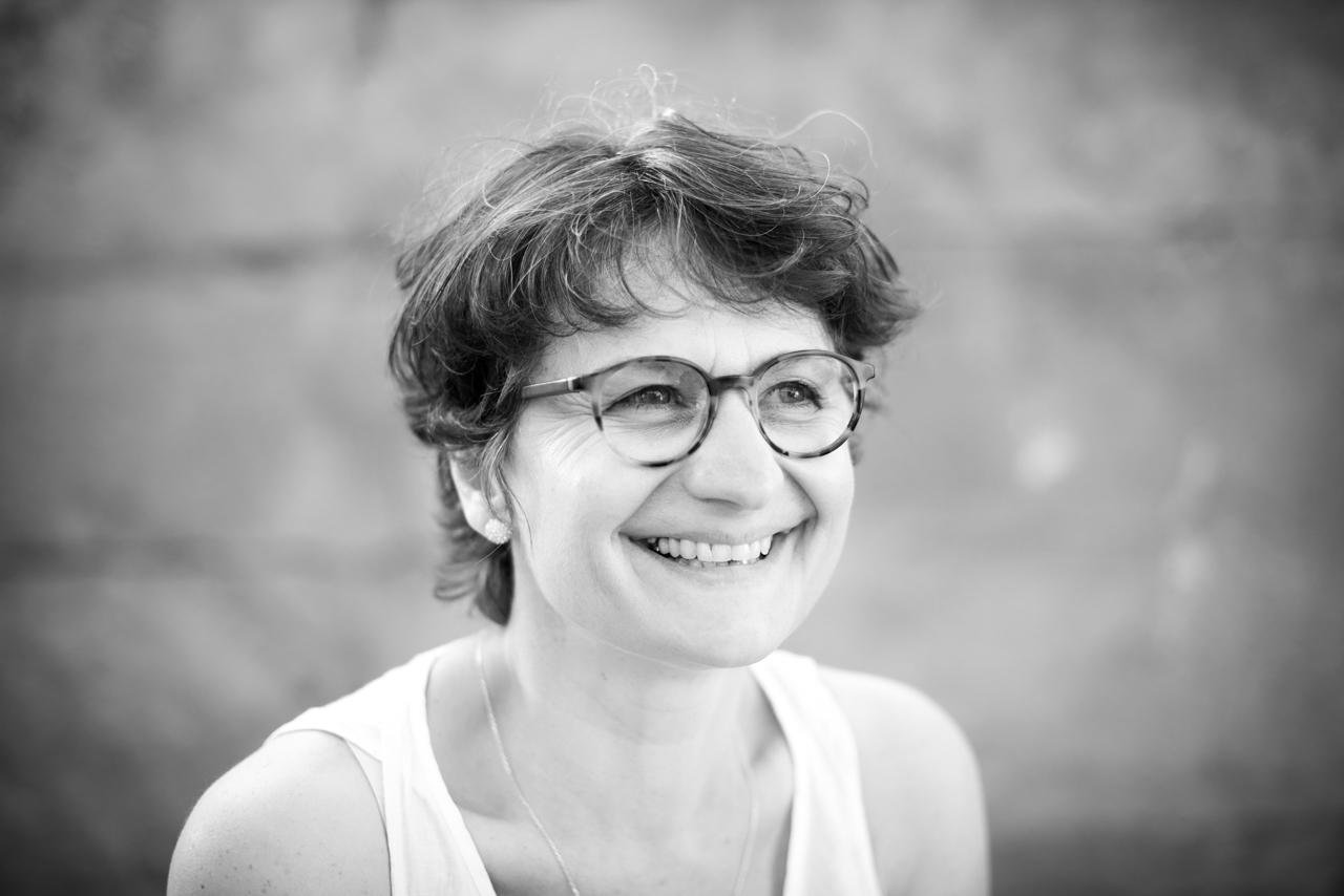 Portrait d'une femme souriante en noir et blanc.