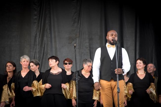 chanteur et choeur en noir et or sur un podium