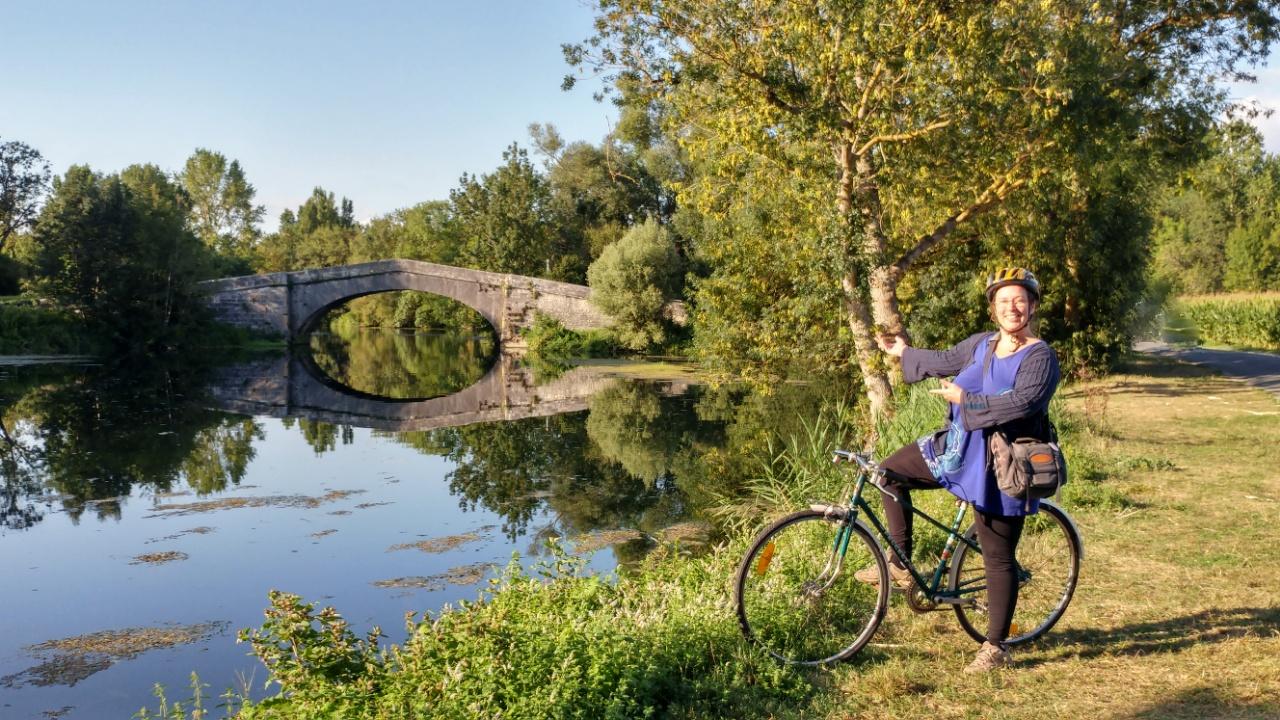 moi à vélo devant un pont gallo-romain sur la Charente