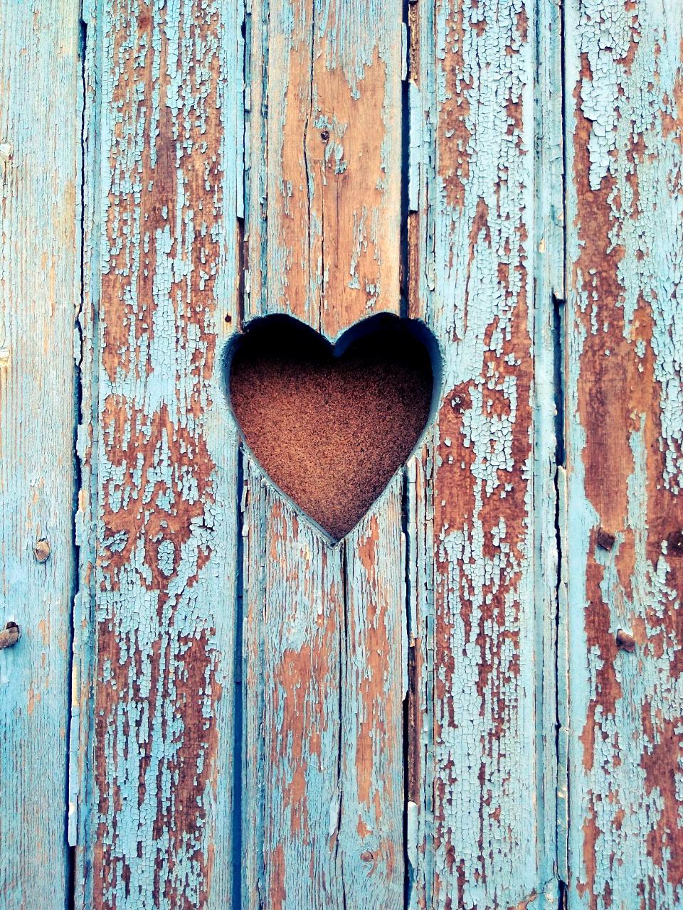 un volet en bois peint en bleu mais dont la peinture est très écaillée et percé d'un trou en forme de coeur